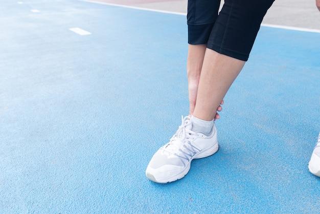 Mão segurando o acidente de lesão no tornozelo entre exercício corrida e corrida na pista de corrida.
