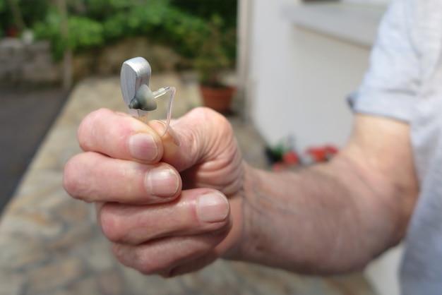 Mão segurando o aparelho auditivo no fundo desfocado