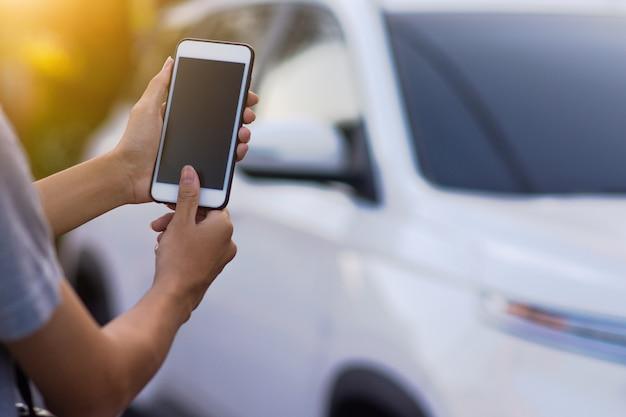 Mão segurando o aplicativo móvel do telefone inteligente para iniciar a tecnologia do carro vida inteligente 5g