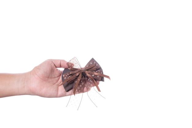 Mão segurando o arco de fita de cabelo castanho