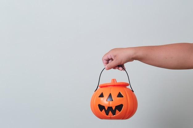 Mão segurando o balde de abóbora de halloween