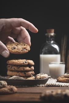 Mão segurando o biscoito de chocolate com um copo e uma garrafa de leite em uma base de madeira