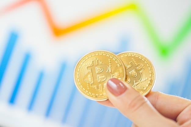 Mão segurando o bitcoin dourado