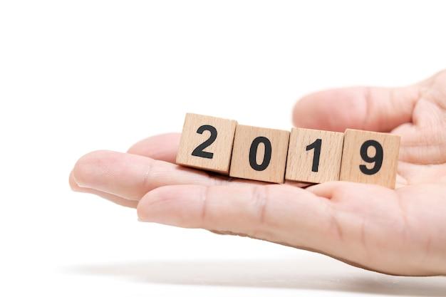 Mão segurando o bloco de madeira 2019 em fundo branco, feliz ano novo conceito