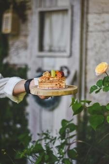 Mão segurando o bolo russo medovik mel no topo morango ang kiwi