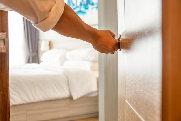 Mão segurando o botão da porta para abrir o quarto.