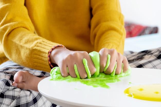 Mão segurando o brinquedo caseiro chamado slime, crianças se divertindo e sendo criativo pelo experimento científico