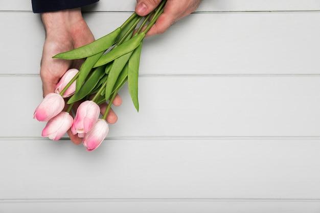 Mão segurando o buquê de tulipas cor de rosa