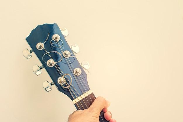 Mão segurando o cabeçote da guitarra