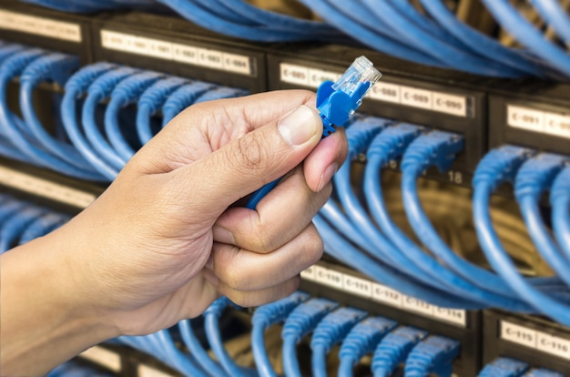 Mão segurando o cabo de rede no hub switch no fundo da sala do servidor
