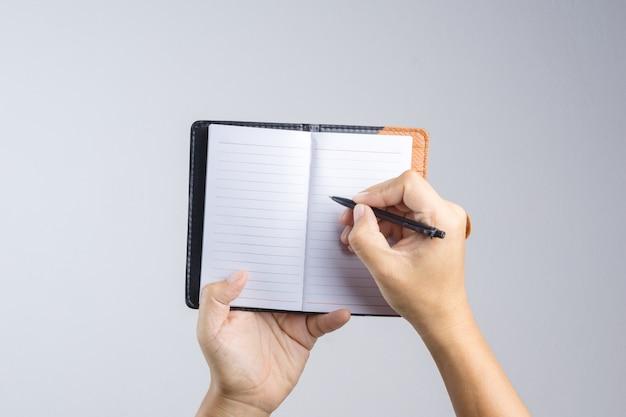 Mão segurando o caderno de papel de capa marrom vintage