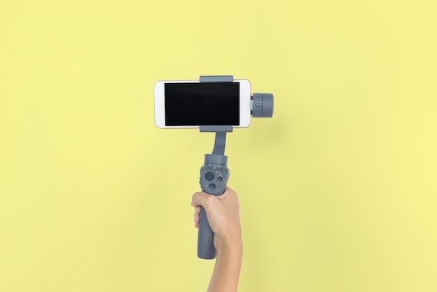 Mão segurando o cardan ou estabilizador com telefone móvel em fundo amarelo pastel