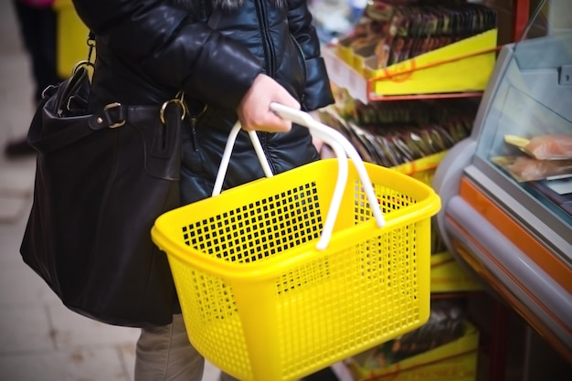 Mão segurando o carrinho de compras vazio