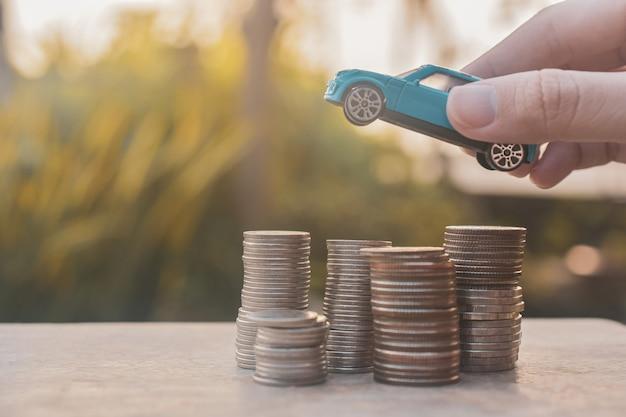 Mão segurando o carro de brinquedo em pilhas de moedas