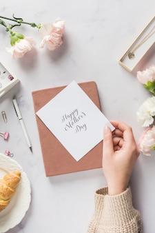Mão segurando o cartão bonito do dia das mães