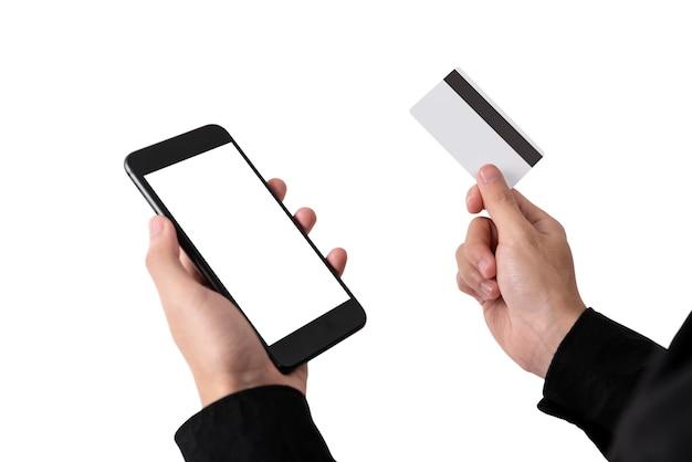 Mão segurando o cartão de crédito branco e a tela em branco do telefone móvel