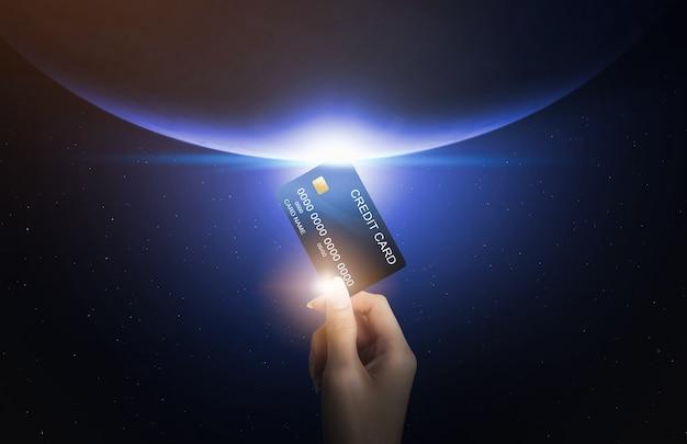 Mão segurando o cartão de crédito e abstrato em todo o mundo conectado ao redor da terra