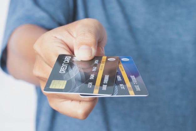 Mão segurando o cartão de crédito e estenda-o para a frente, isolado no branco.