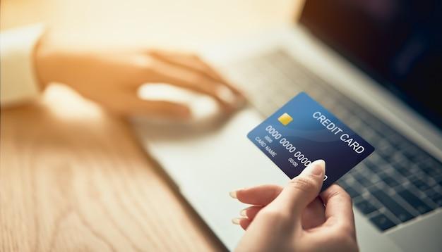 Mão segurando o cartão de crédito e pressione o computador portátil digite o código de pagamento para o produto.