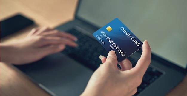 Mão segurando o cartão de crédito e pressione o laptop, digite o código de pagamento do produto