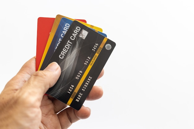 Mão segurando o cartão de crédito isolado no branco