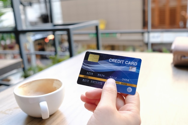 Mão segurando o cartão de crédito no café