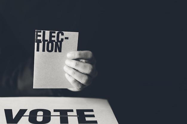 Mão segurando o cartão de eleição e voto caixa, conceito de democracia, tom preto e branco