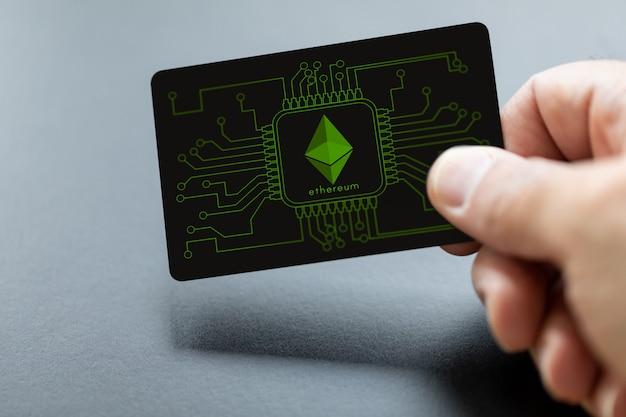 Mão segurando o cartão de pagamento ethereum