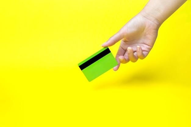 Mão segurando o cartão de visita, maquete, sobre fundo amarelo.