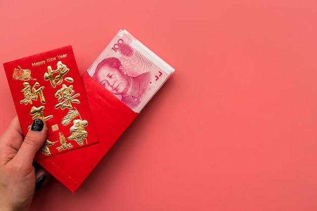 Mão segurando o cartão e as contas chinesas