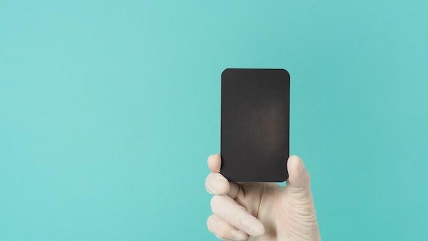 Mão segurando o cartão preto em branco vazio. mão com terno ppe, luva de látex em fundo verde ou azul tiffany. espaço vazio para texto