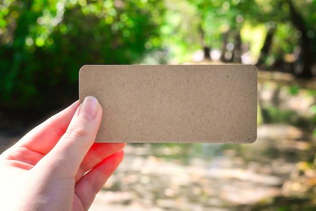 Mão segurando o cartão vazio no parque em raios de sol. fundo. copie o espaço.
