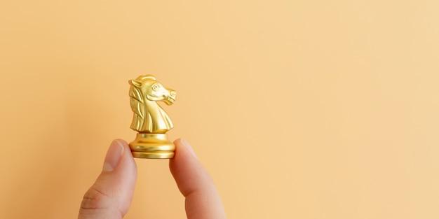 Mão segurando o cavaleiro de xadrez dourado