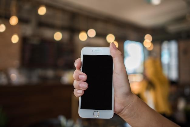 Mão segurando o celular branco com tela preta em branco