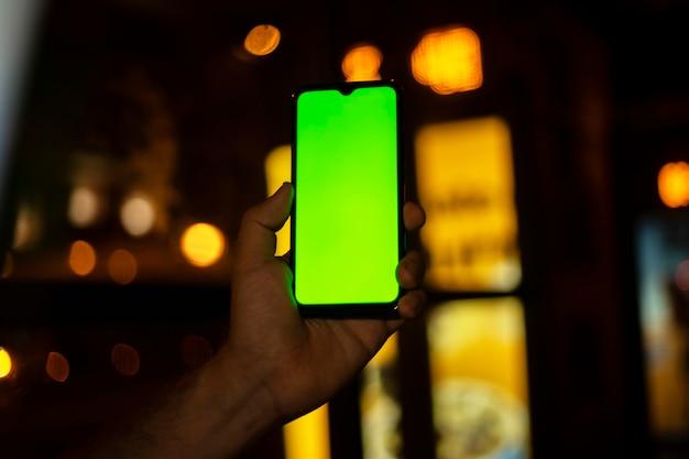 Mão segurando o celular com a tela da câmera na cidade à noite com as luzes do carro no fundo