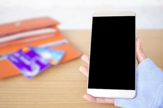 Mão segurando o celular com desfoque de imagem de cartão de crédito e carteira. copie o espaço para adicionar a apresentação do texto.