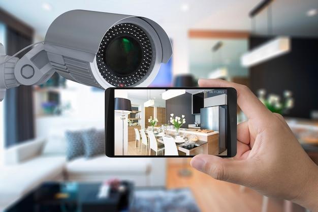 Mão segurando o celular se conectar com a câmera de segurança