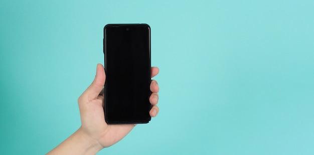 Mão segurando o celular sobre fundo verde hortelã.