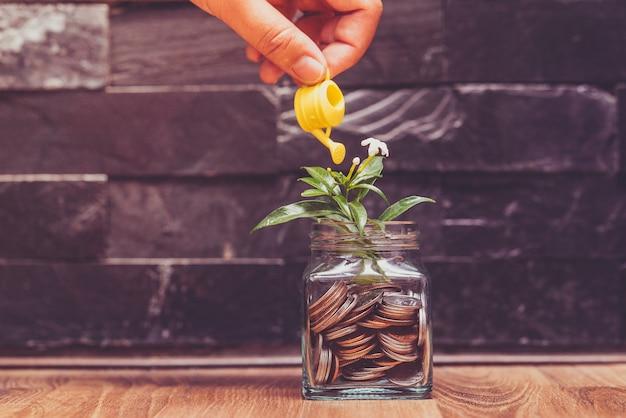 Mão segurando o chuveiro para investimentos em crescimento de dinheiro no fundo da parede de cimento em tom vintage