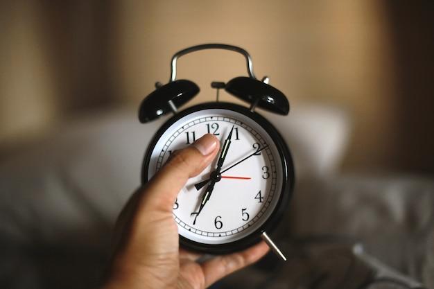 Mão segurando o clássico despertador preto mostrando sete horas com fundo desfocado