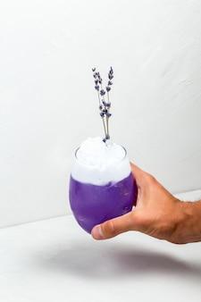 Mão segurando o cocktail de espuma de lavanda roxo incomum
