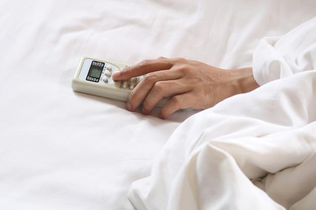 Mão segurando o controle remoto de ar condicionado na cama