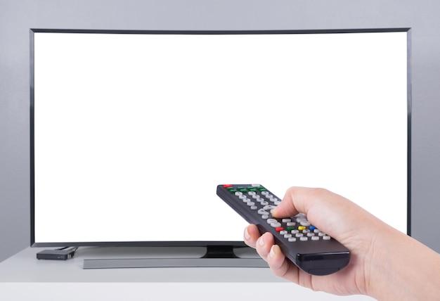 Mão segurando o controle remoto de tv com tv led e tela branca