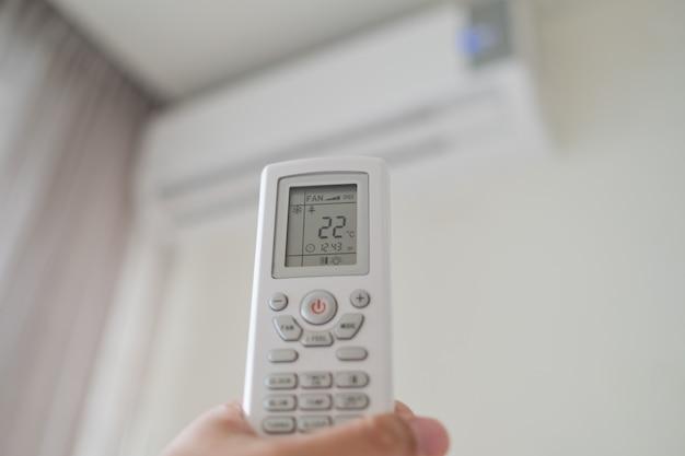 Mão segurando o controle remoto do ar condicionado