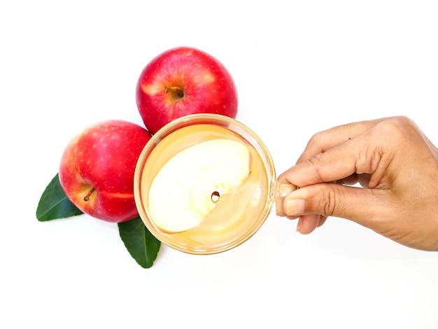 Mão segurando o copo da bebida com chá de maçã ou vinagre de maçã