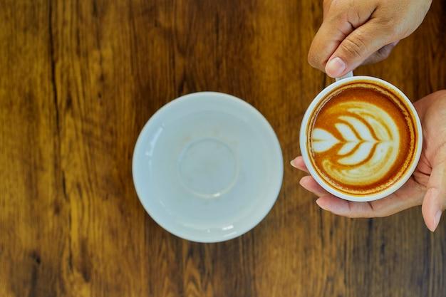 Mão segurando o copo de café na mesa