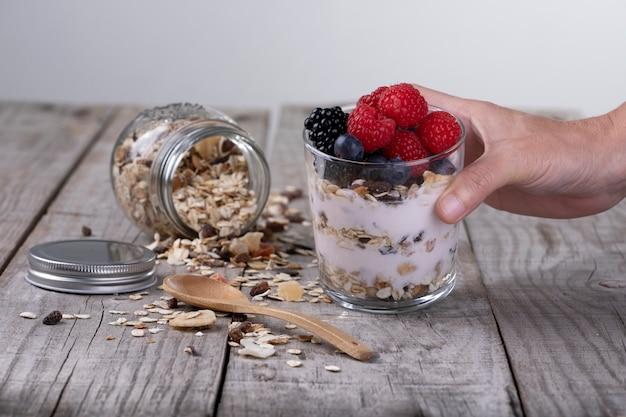 Mão segurando o copo de cereal com iogurte e frutas da floresta, conceito de café da manhã saudável