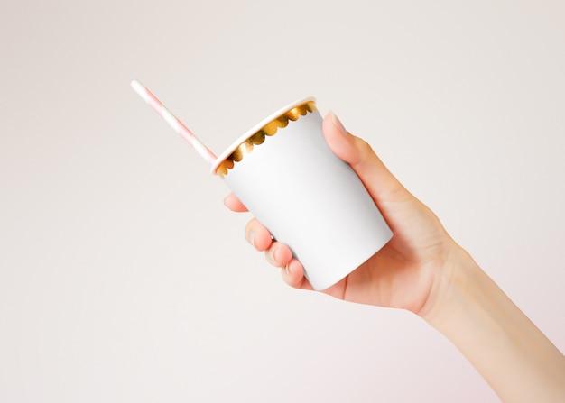Mão segurando o copo de papel com palhas no fundo