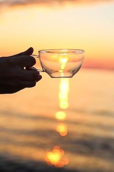 Mão segurando o copo de vidro na frente do pôr do sol