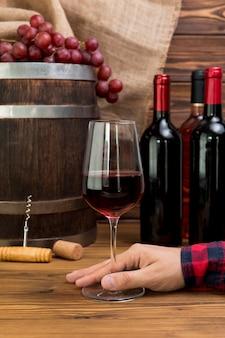 Mão segurando o copo de vinho com garrafas e barre